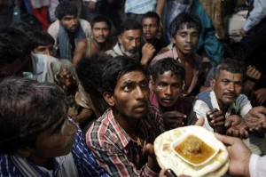 Homeless Indian men wait to receive food.