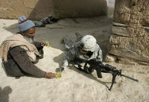 A soldier gets offered tea by an Afghan man.
